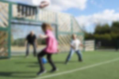 Vater und Kinder beim Ballspielen auf dem Allzweckplatz von Lalandia